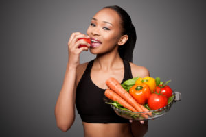 young attractive fit woman smiling biting into a tomato